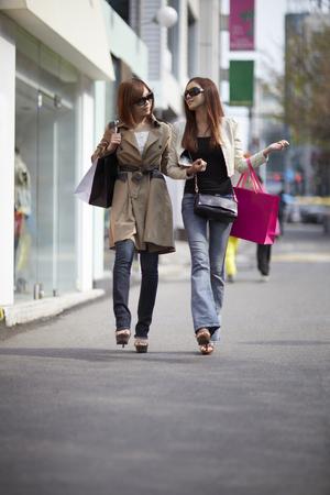 cuerpo entero: Una mujer joven, joven de compras con un amigo