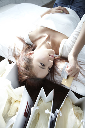 fiend: A Young woman,young Lying On Her Bed With Shopping Bags Next To Her Bed