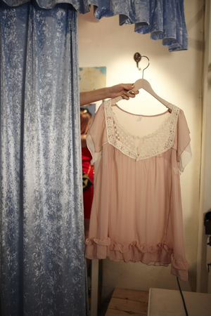 'hide out': A Young woman,young Hiding Behind The Curtains Of The Changing Room