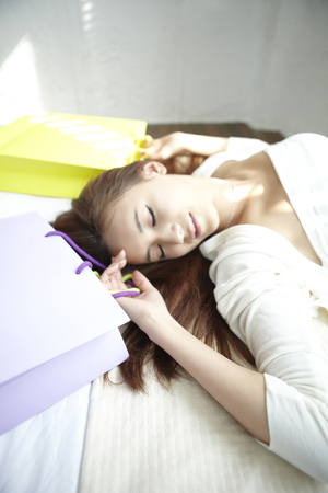 fiend: A Young woman,young Lying On Her Bed With Shopping Bags Stock Photo