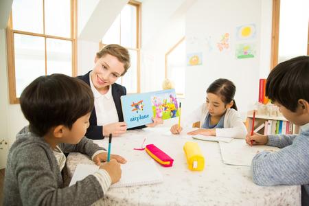 外国人の女性先生と英語を学ぶ若い学生たち