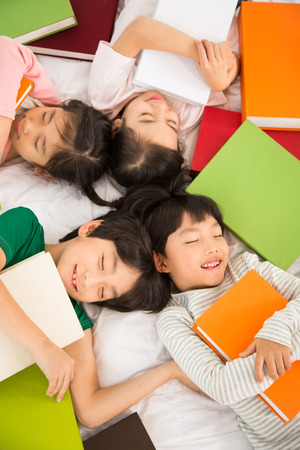 backs: Young Students Lying On Their Backs With Piles Of Books Stock Photo