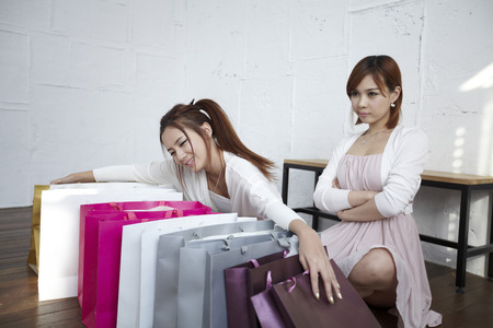fiend: Two Young Women With Shopping Bags Placed In Front Of Them Stock Photo