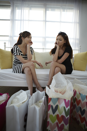 Two Women Relaxing On Couch After A Day Of Shopping Stock Photo