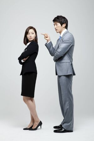 standing together: Male And Female Coworkers In Studio Setting Stock Photo