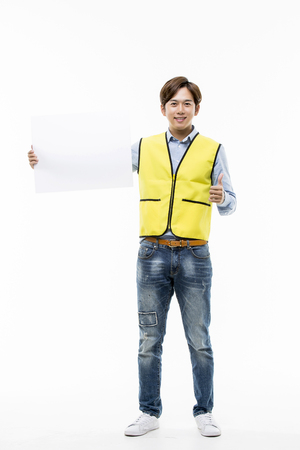 Young Male College Student In Work Vest Holding Up A Blank Sign Stock Photo