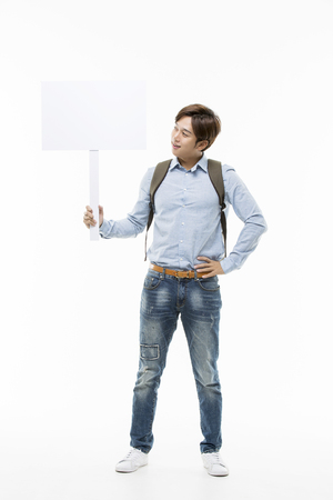Young Male College Student Holding Up A Blank Sign Stock Photo