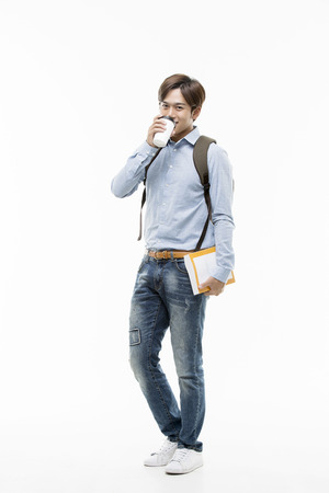 Young Male College Student Standing With A Cup And A Book