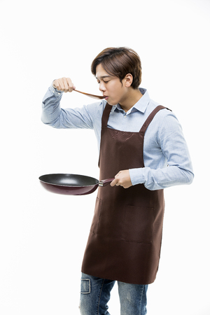 Young Male In Apron Holding A Pan