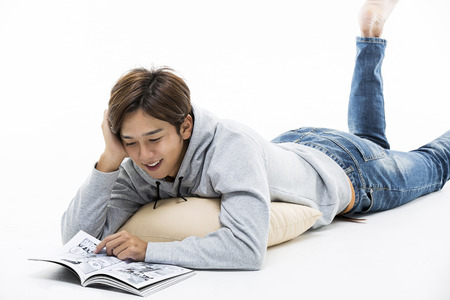 Young Male Lying On Stomach Reading A Comic Book