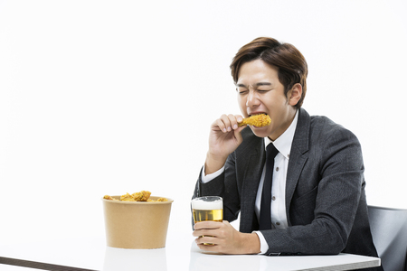 Young Businessman Having Chicken And Beer