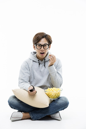 Young Male Sitting And Eating Popcorn While Watching A Movie