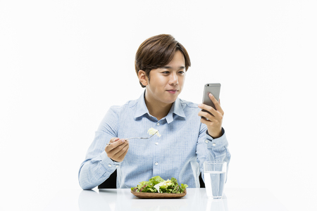 office time: Young Male Eating Salad Stock Photo