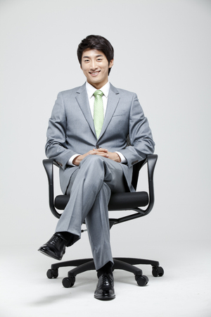 Young Businessman In Full Suit Sitting