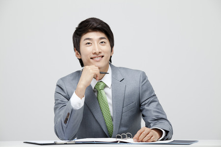 businessman thinking: Young Businessman In Full Suit At The Desk Stock Photo