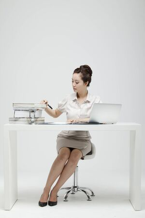 Young Businesswoman With Jacket Off Sitting At A Desk