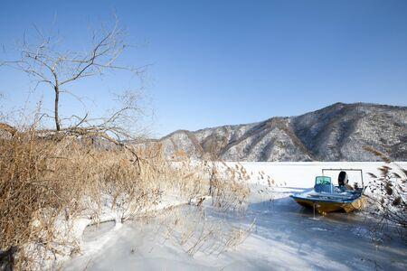 frozen river: Fishing boat on Frozen river (paroho Lake), Gangwondo Hwacheon South Korea