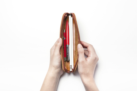 ball pens stationery: A leather pencil case with two hands - isolated on white