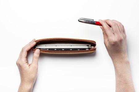 ball pens stationery: Una caja de lápiz de cuero con dos manos - aislados en blanco