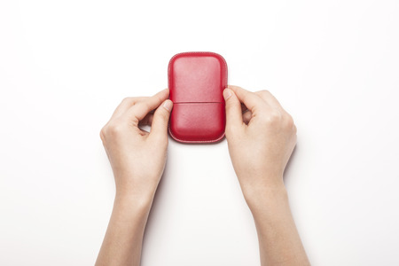 Close up shot of a red leather business card holder with hands-isolated on white Stock Photo