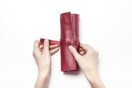 Close up shot of a red leather roll up pencil case-isolated on white Stock Photo