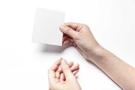 Close up shot of hands holding a piece of white paper-isolated on white
