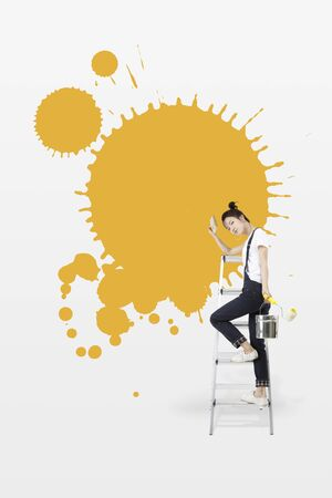 Asian girl painting the wall yellow