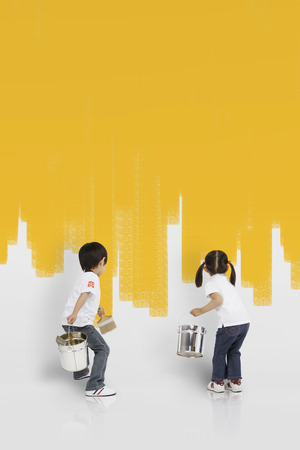 Asian kids painting the wall yellow