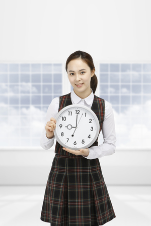 Asian girl holding a clock