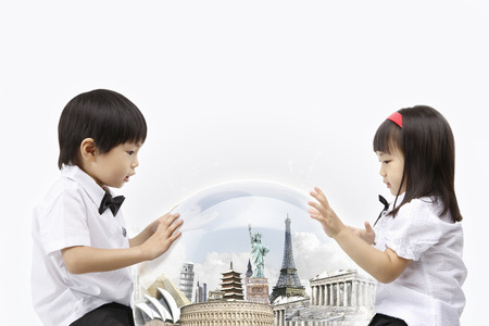 Asian kids looking down at landmarks in glass dome 版權商用圖片