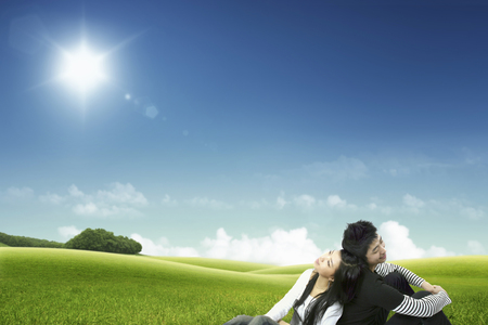 Asian couple relaxing on the grass Stock Photo