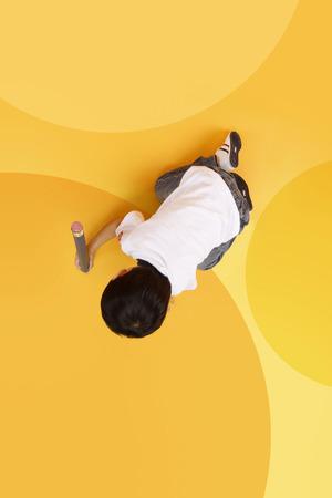 Aziatische jongen die op de vloer met een reusachtig potlood schrijft Stockfoto