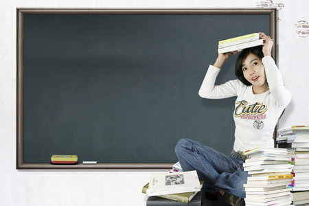 Asian female student posing with a few books Editorial