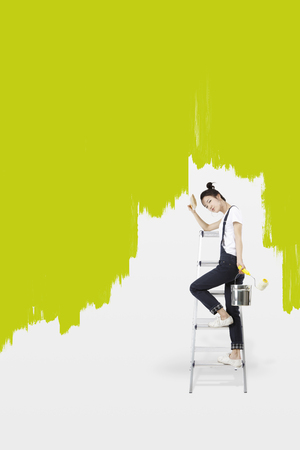 Asian girl painting green on the wall