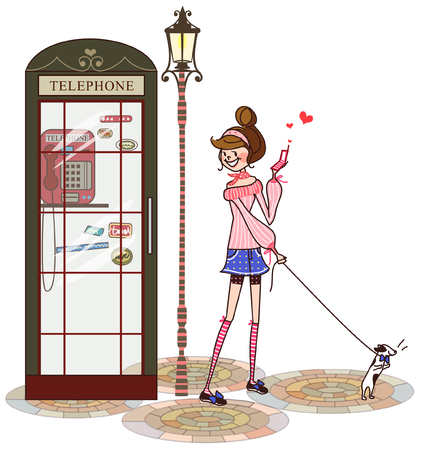 woman cellphone: Woman standing near a telephone booth and holding a mobile phone
