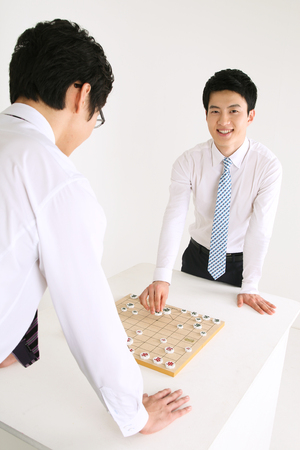Asian business man playing Korean traditional chess, Janggi - isolated on white