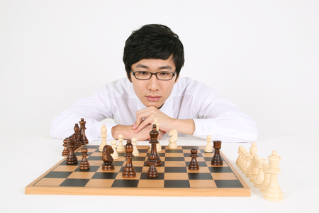 Asian business man with chess pieces - isolated on white