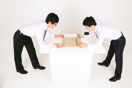 Asian business man playing Asian board game, go - isolated on white