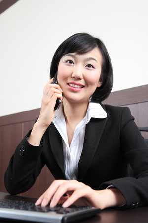 telephone interview: Young Asian business people at work Stock Photo