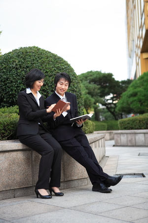 customer records: Young Asian business people outside the office