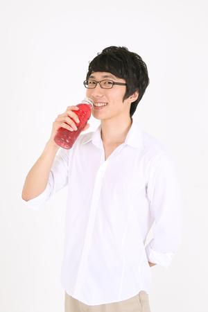 서서 병에서 주스를 마시는 젊은 아시아 사람 스톡 콘텐츠