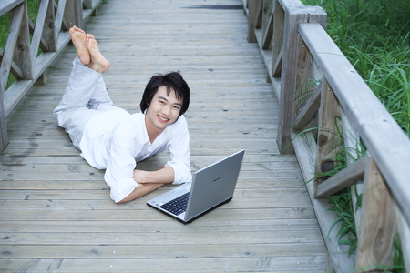 Young Asian man lying on the wooden bridge, working on his laptop Editorial