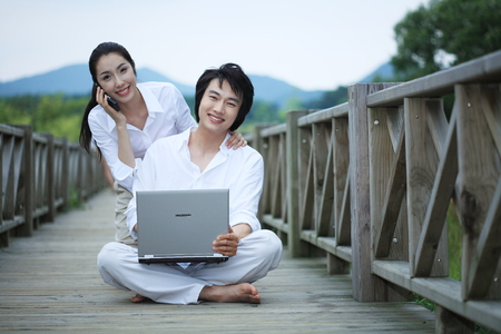 ourdoor: Young Asian couple working on a laptop on the wooden bridge