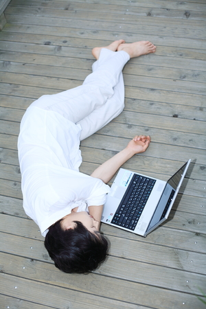 ourdoor: Young Asian man lying on the wooden bridge, working on his laptop Editorial