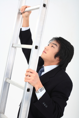 CHALLENGING: Asian businessman posing  with a ladder in the studio- isolated on white