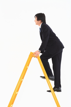 CHALLENGING: Asian businessman posing with a yellow ladder in the studio - isolated on white