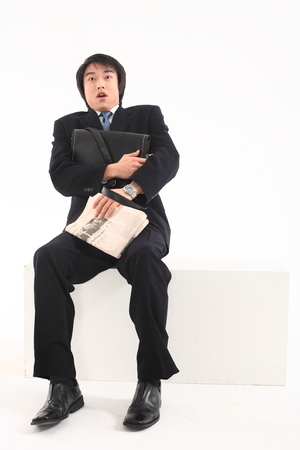 Asian businessman sitting with his briefcase and newspaper - isolated on white
