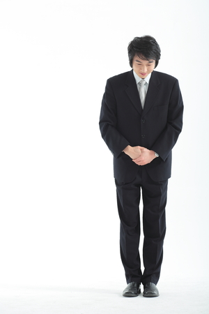 experiencing: Asian businessman taking a bow - isolated on white