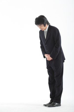 Asian businessman taking a bow - isolated on white