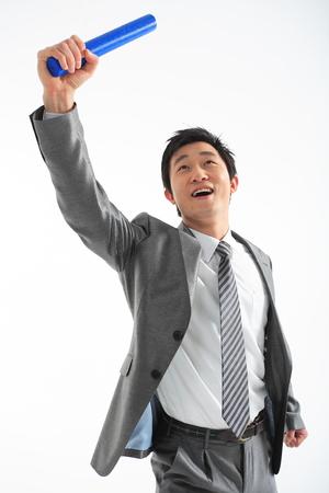 Aziatische zakenman die met een relaisknuppel loopt - die op wit wordt geïsoleerd Stockfoto